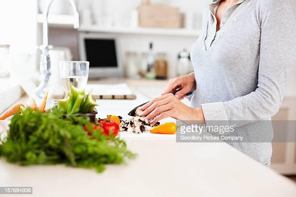 Reife Frau Schneiden Gemüse in der Küche