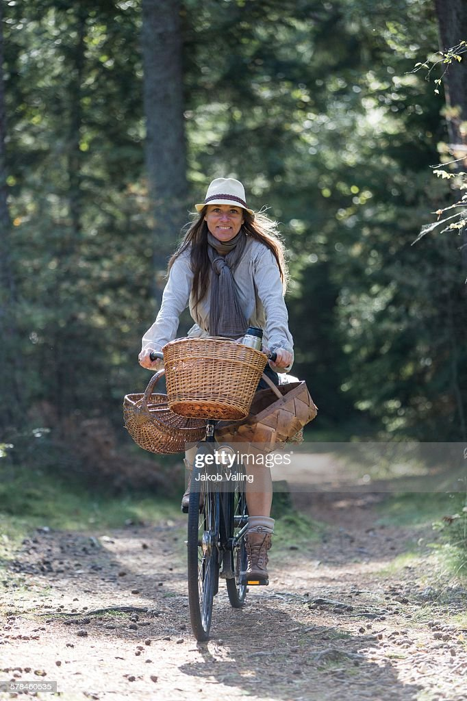 Mature woman cycling with foraging baskets on forest path