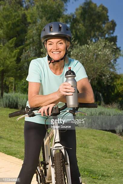 Reife Frau Radfahrer mit Helm und holding Flasche