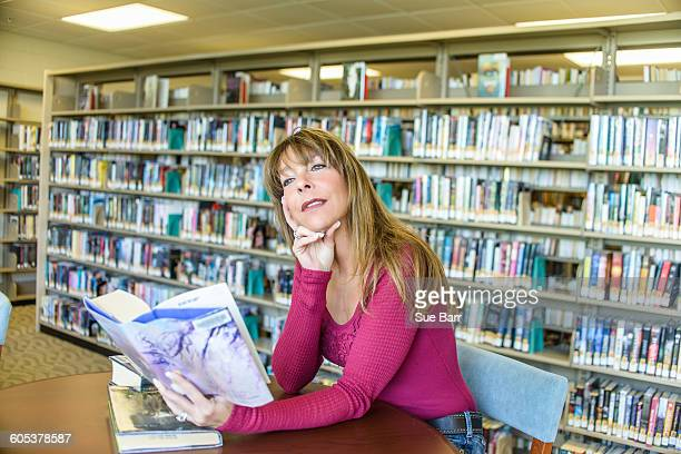 Mature woman daydreaming whilst reading in library