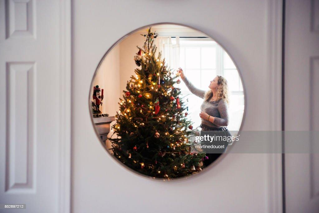 Mature woman decorating Christmas tree at home. : Stock Photo