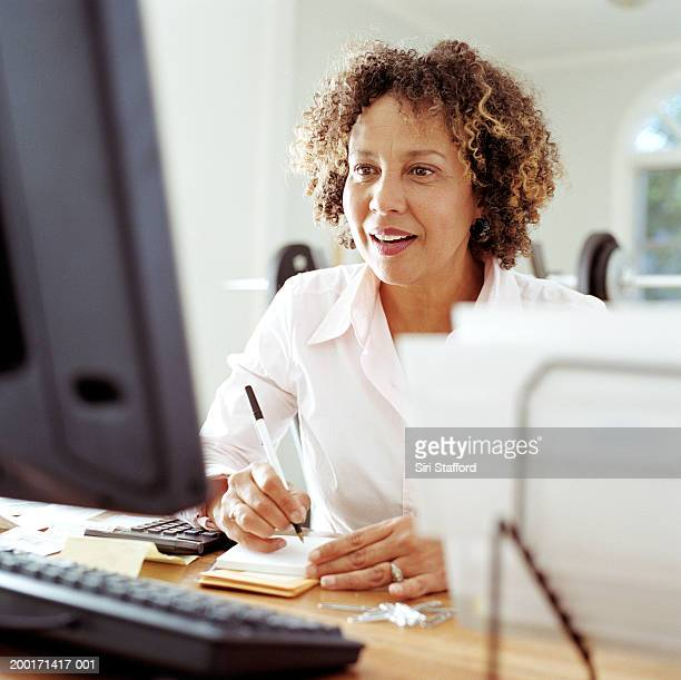 Mature woman doing finances in home office