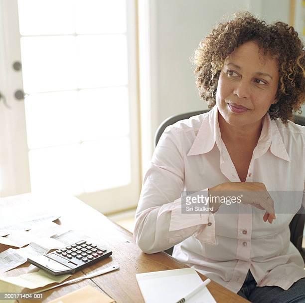 Mature woman doing finances in  home office, portrait