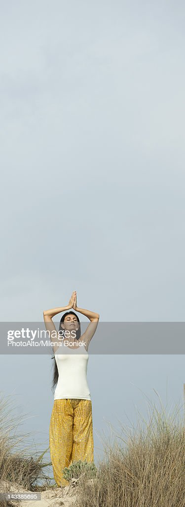 Mature woman doing prayer yoga position on beach