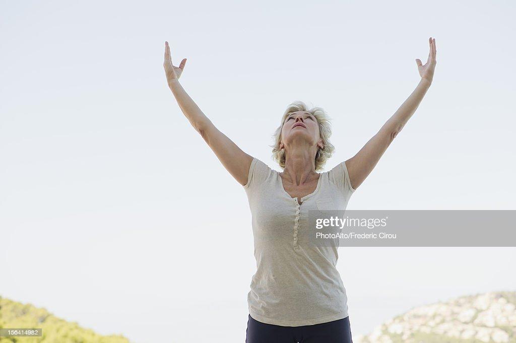Mature woman doing sun salutation