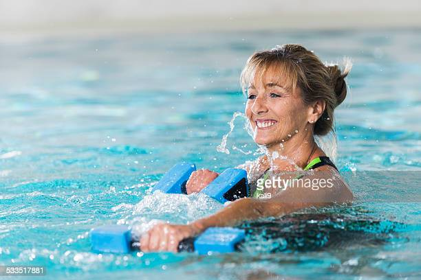 Mature woman doing water aerobics with dumbbells