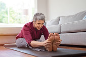 Beautiful senior woman doing stretching exercise while sitting on yoga mat at home. Mature woman exercising in sportswear by stretching forward to touch toes. Healthy active lady doing yoga and flexib