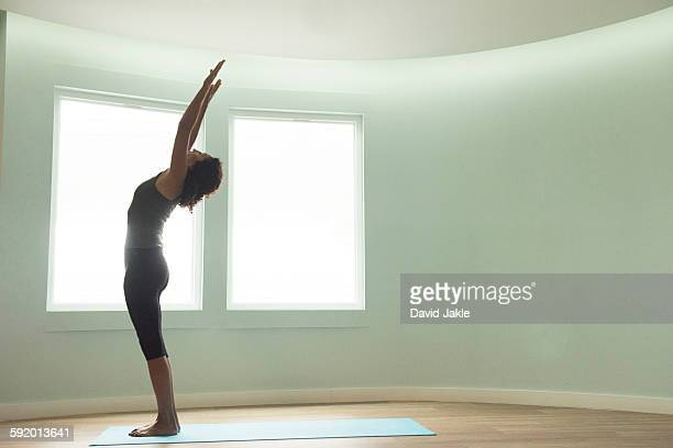 Mature woman doing yoga in curved room
