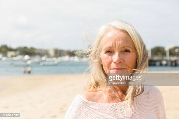 Mature woman dreaming on the beach, copy space