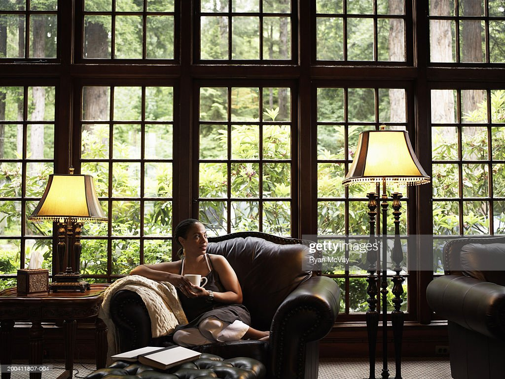 Mature woman drinking coffee on leather armchair in lobby of lodge : Stock Photo
