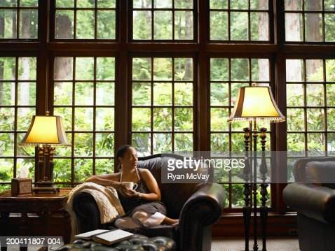 Mature woman drinking coffee on leather armchair in lobby of lodge