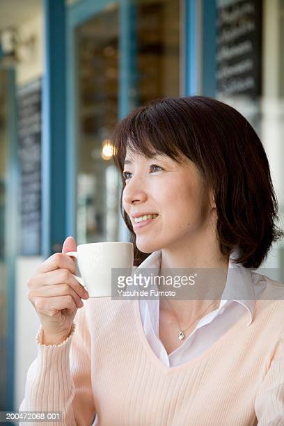 Mature woman drinking cup of coffee, smiling, looking away