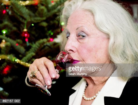 Mature woman drinking liquer from small glass