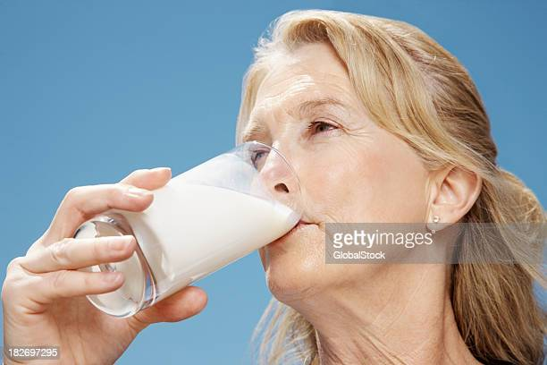 Mature woman drinking milk against blue sky