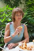 Mature woman drinking orange juice at breakfast in garden, smiling