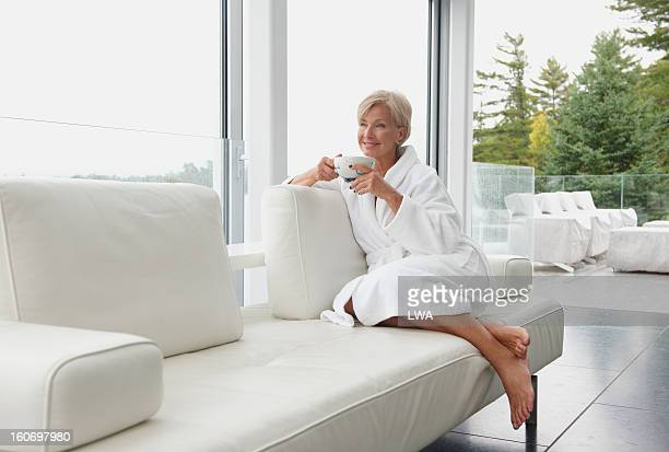 Mature woman drinking tea on couch