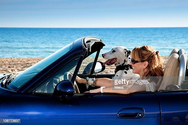 Mature woman driving an sports car with her dog