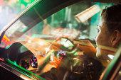 Mature Woman Driving Car, City Lights Reflected