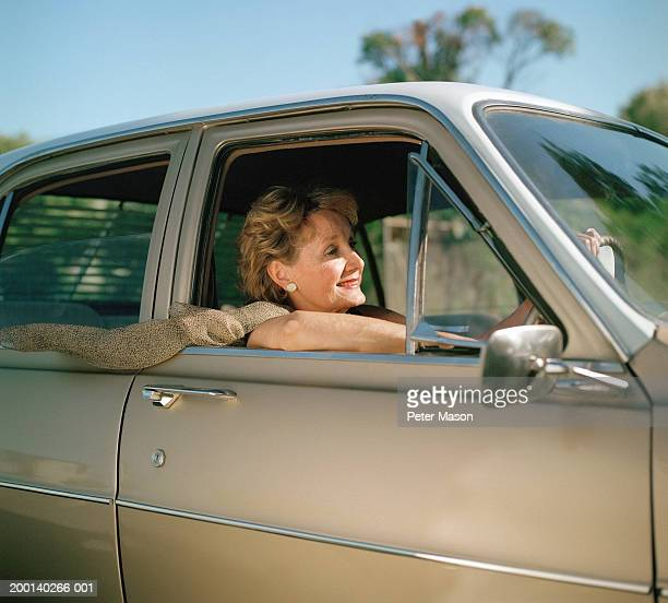 Mature woman driving car, scarf flying in the breeze