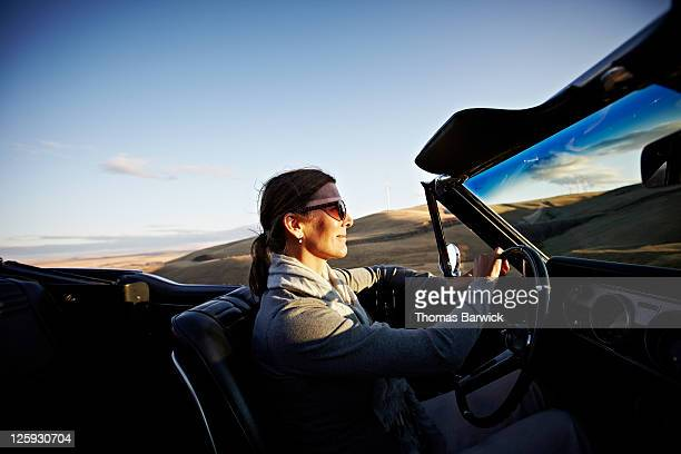 Mature woman driving convertible at sunset