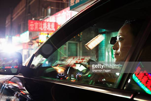 Mature Woman Driving Through Bustling City Center