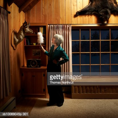 Mature woman dusting with feather duster : Bildbanksbilder