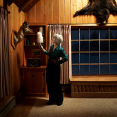 Mature woman dusting with feather duster