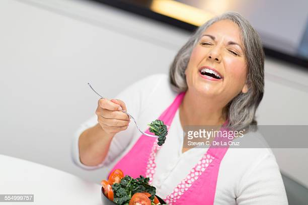 Mature woman eating bowl of tomatoes and kale