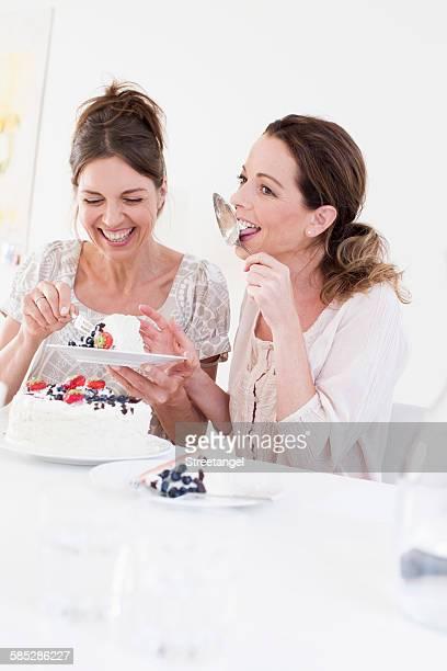 Mature woman eating cake, licking cake server smiling