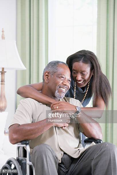 Mature woman embracing a mature man from behind sitting in a wheelchair and smiling