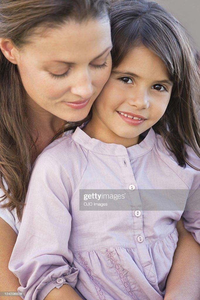 Mature woman embracing daughter : Stock Photo