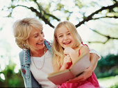 Mature woman embracing granddaughter outdoors, smiling