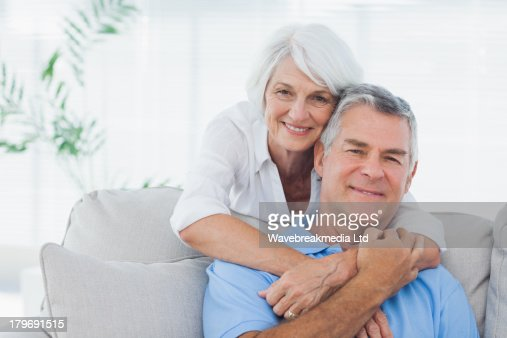Woman embracing husband sitting on the couch : Foto de stock