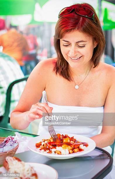 Mature woman enjoying a Poutine at downtown Montreal cafe