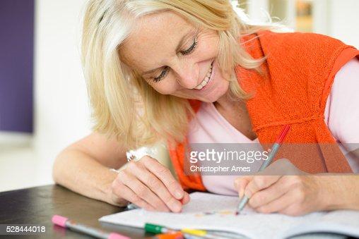 Mature Woman Enjoying Adult Colouring Book