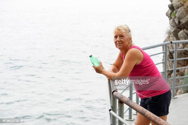 Mature  woman exercise outdoors by the sea