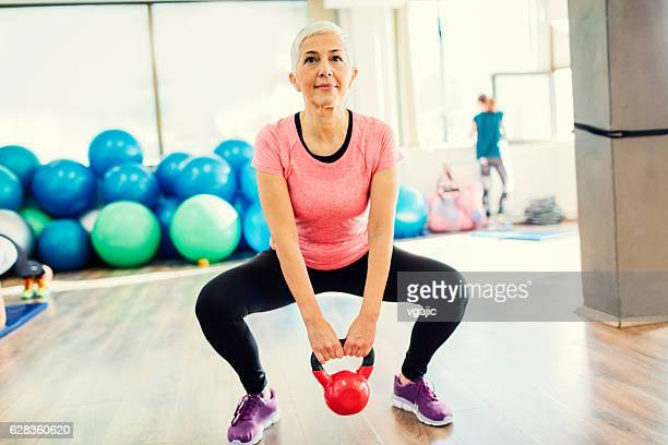 Mature Woman Exercising In Gym With Kettle Bell.
