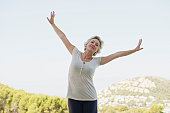 Mature woman exercising with arms outstretched