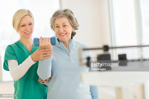 Mature woman exercising with personal trainer, Jersey City, New Jersey, USA