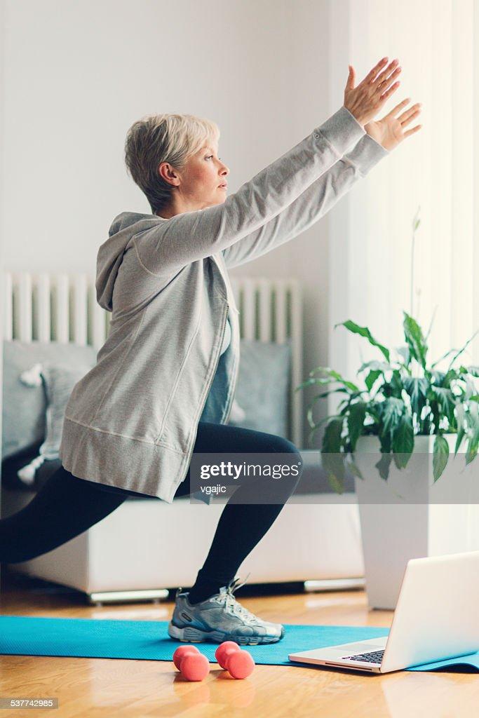 Mature Woman Exercising Yoga At Home.