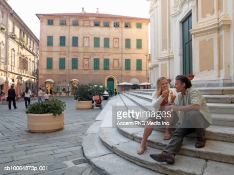 Mature woman feeding ice cream to man on steps : Stock Photo
