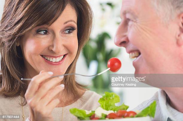 Mature woman feeding man salad