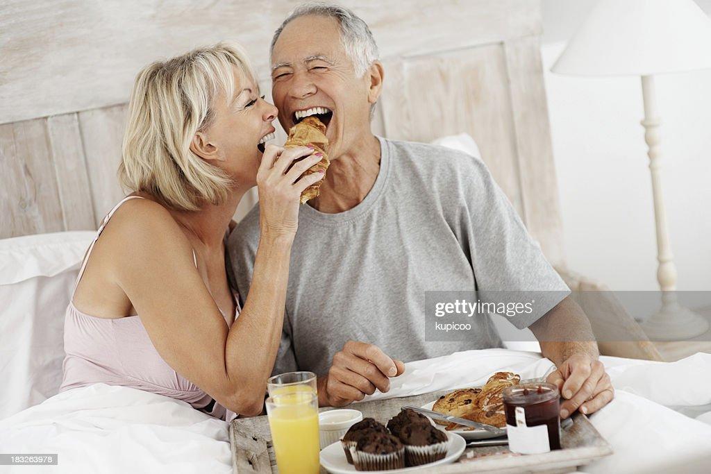 Ältere Frau Füttern älteren Mannes, während ein Frühstück im Bett : Stock-Foto