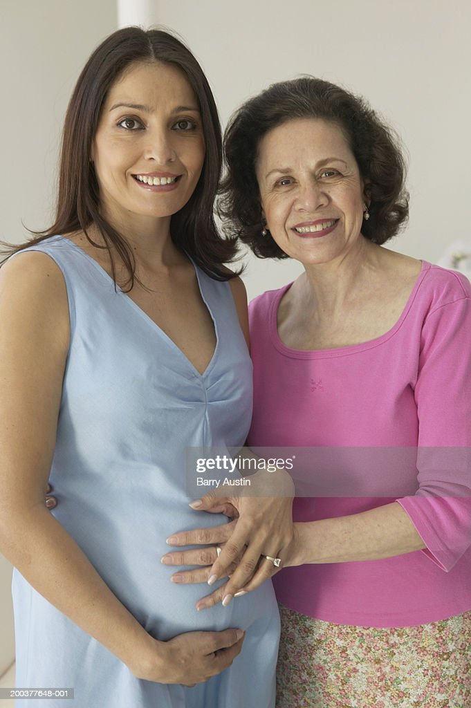 Mature woman feeling pregnant woman's bump, smiling, portrait