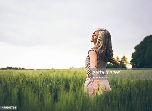 Mature woman feeling youthful in a lush summer field
