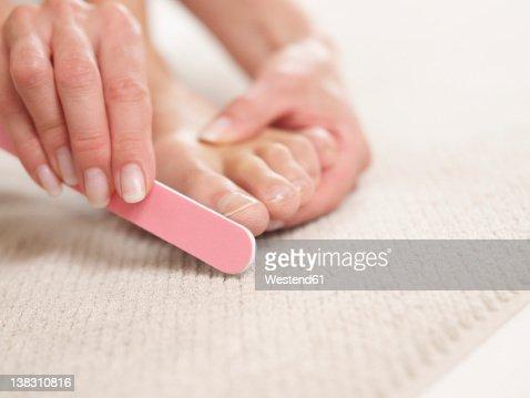 Mature woman filing nails, close up
