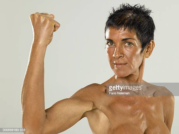 Mature woman flexing bicep, portrait, close-up