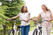 Two mature women in conversation while walking with bicycle at park. Happy beautiful senior women walking in the park with bicycles in a spring time. Friends holding bikes and talking to each other.'r