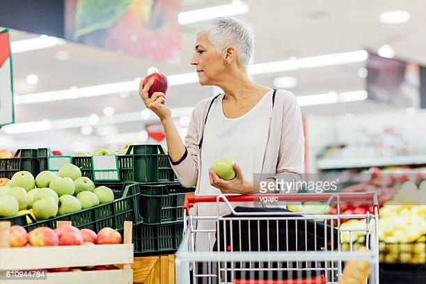 Mature Woman Fruits Shopping In Local Market.
