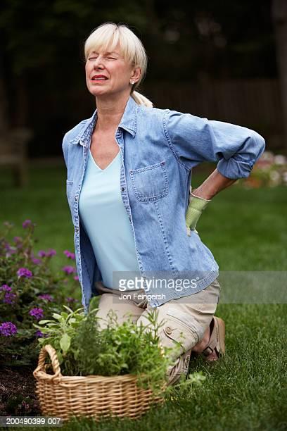 Mature woman gardening, grabbing lower back, grimacing